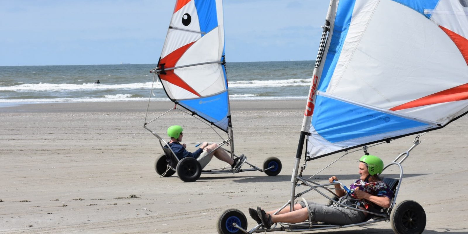 two people driving wind-powered cars on a beach shoreline