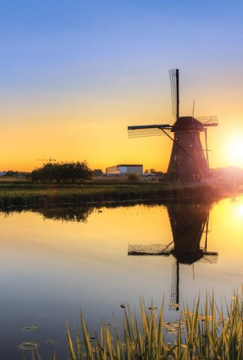 The sunsets over a windmill in the Netherlands. Tour landscapes like this and so much more with us.