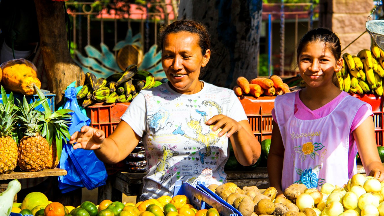 Shoppers in Nicaragua market look at fruit