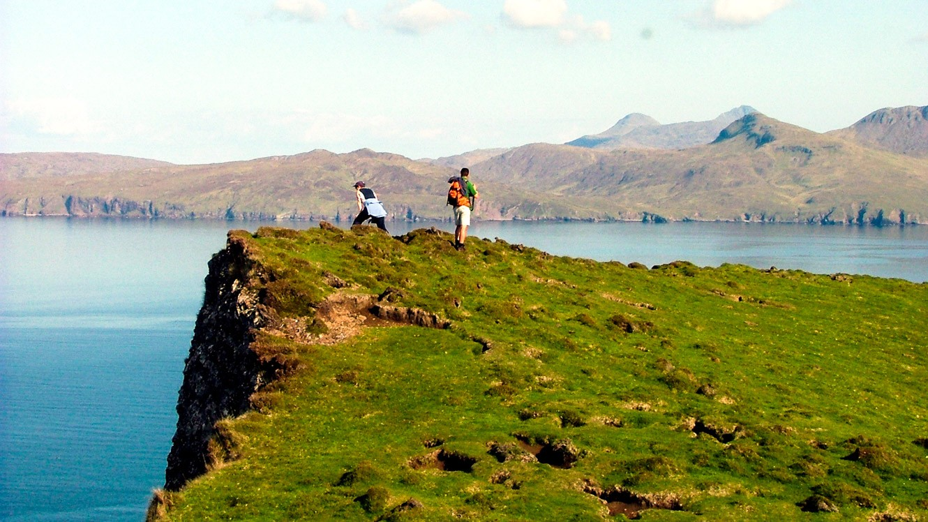 Hikers stand on Scotland bluff by lake