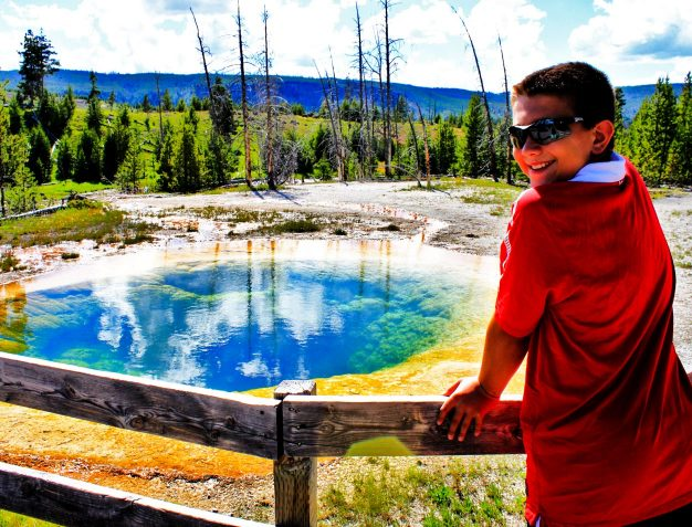 boy turns head at camera while Yellowstone National Park is in background