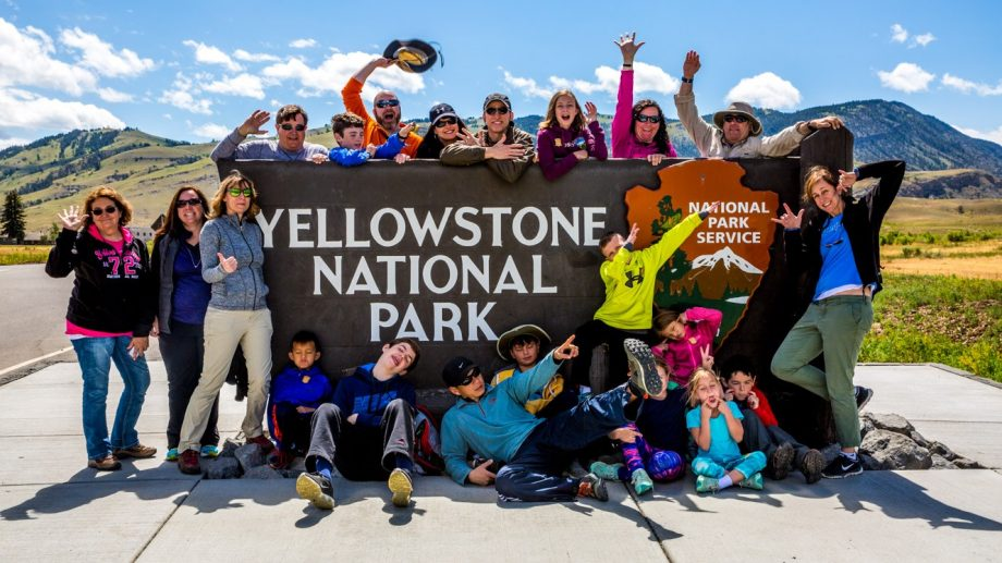 Group of travelers gather around Yellowstone National Park sign