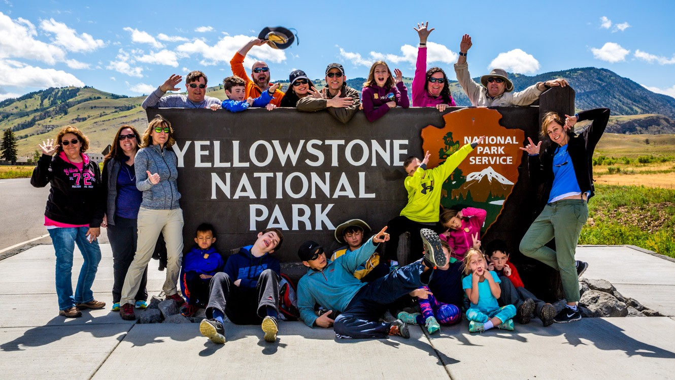 Group of travelers gather around Yellowstone National Park sign. They are Enjoying one of our best Wyoming Vacations